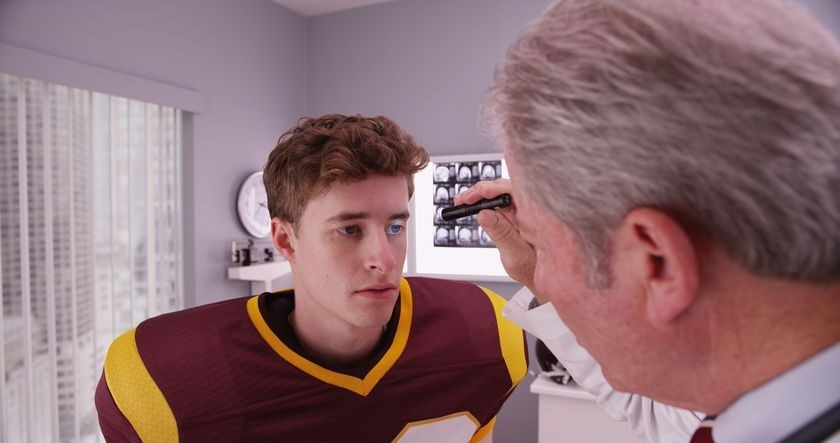 Doctor examining the left eye of football player for a concussion
